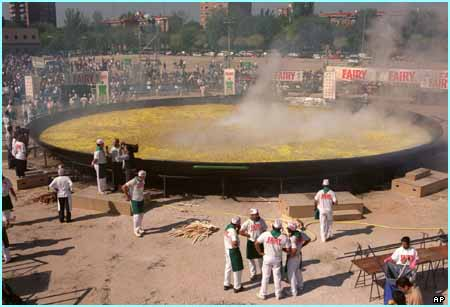 Steam rises from a giant Paella dish that organizers claim to be the World's biggest, Madrid Spain Oct. 2, 2001. The paella, measuring 400 square meters (480 square yards), was made with 6.000 kilos (13.200 pounds) of rice, 11.000 kilos (24.200 pounds) of olive oil, 12.500 kilos (27.500 pounds) of chicken and rabbit, 5.000 kilos (11.000 pounds) of vegetables, 300 kilos (660 pounds) of salt, 26 kilos (57 pounds) of peppers, 16 kilos (35 pounds) of colourant and 1 kilo (2 pounds) of ground azafran. (AP Photo, EFE/Ballesteros) **SPAIN OUT**